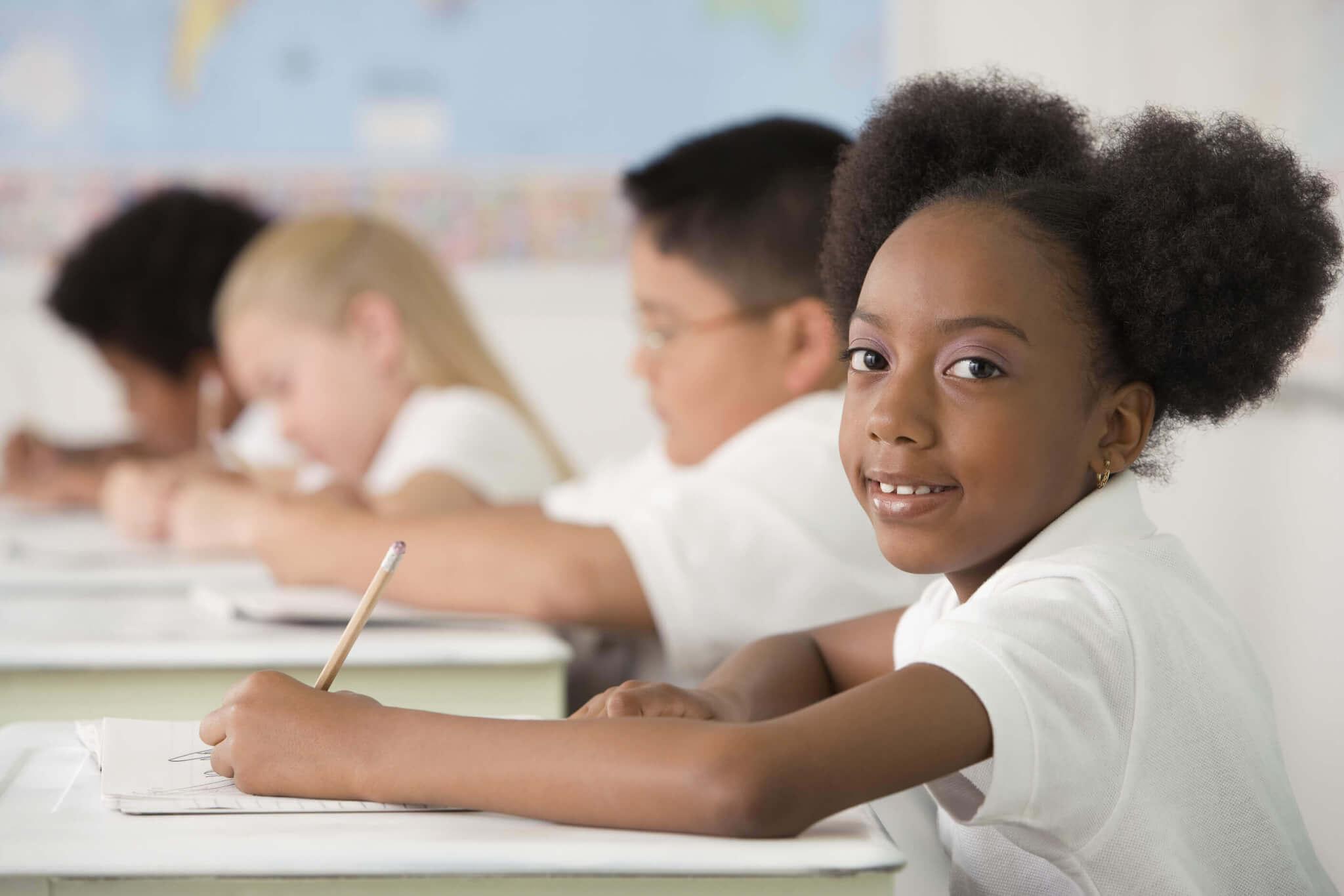 Multi-ethnic-children-writing-at-desks-in-classroom